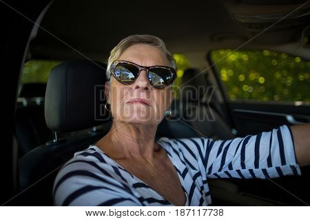 Portrait of serious senior woman driving car