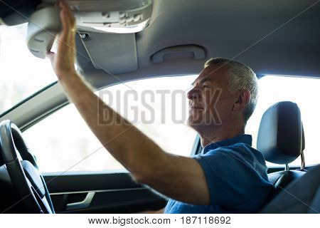 Smiling senior man adjusting rear view mirror in car