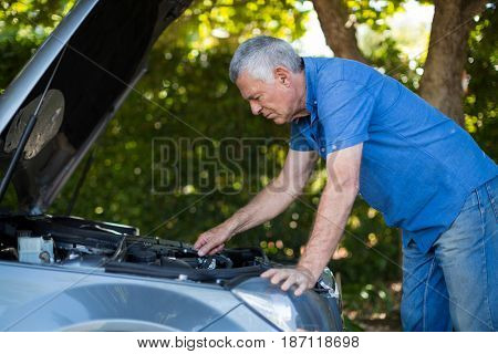 Tensed senior man checking engine of breakdown car