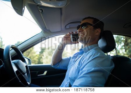 Smiling man talking on phone driving car