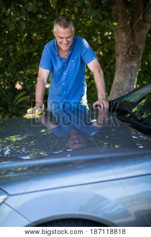 Happy senior man cleaning car in yard