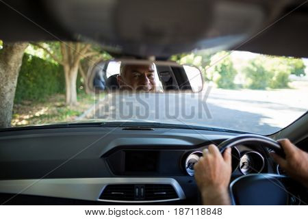 Reflection of senior man on rear view mirror in car