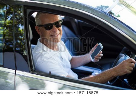 Portrait of smiling senior man using mobile phone while sitting in car