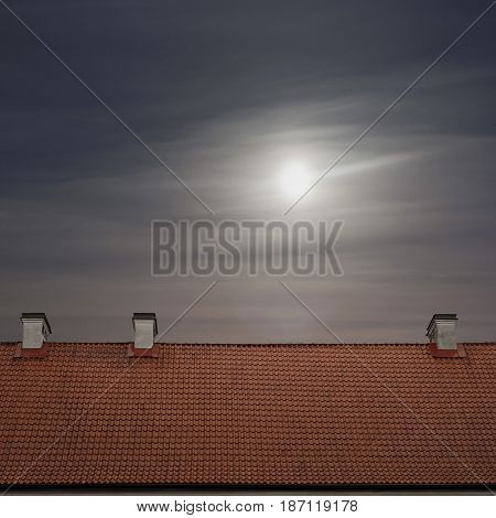 tiled top of the roof, cloudy blue sky and the moon at night