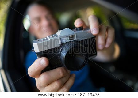 Man photographing with camera while sitting in car