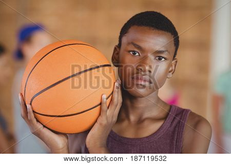 Determined high school boy standing with basketball in the court