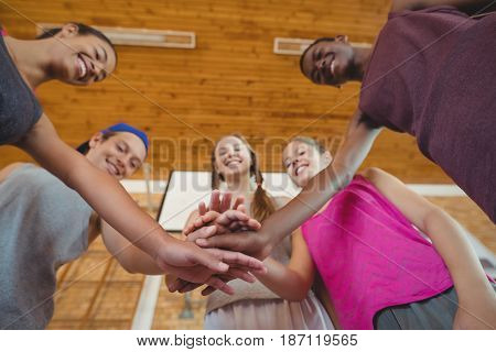 High school kids with their hands stacked in basketball court