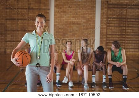 Portrait of female coach standing with basketball in basketball court