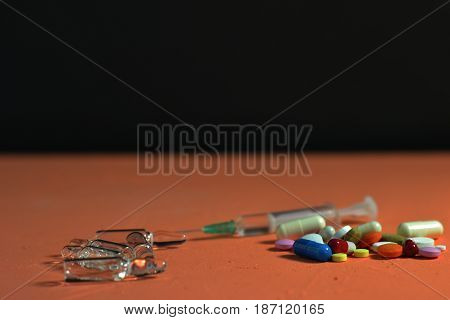 Medical ampules, tablets and syringes on a peach background.
