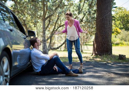 Frustrated woman shouting on man sitting by breakdown car
