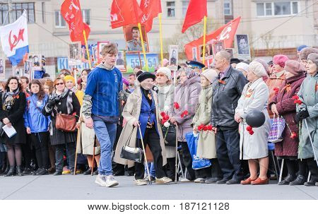 Kirishi, Russia - 9 May, A volunteer leads an elderly woman, 9 May, 2017. Holding a festive rally dedicated to the Victory Day.