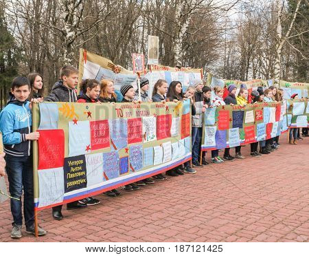 Kirishi, Russia - 9 May, Teenagers with posters for the Victory Day, 9 May, 2017. Laying wreaths and flowers in memory of the fallen at the Eternal Flame.