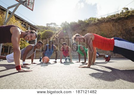 Basketball players performing push up exercise in basketball court outdoors