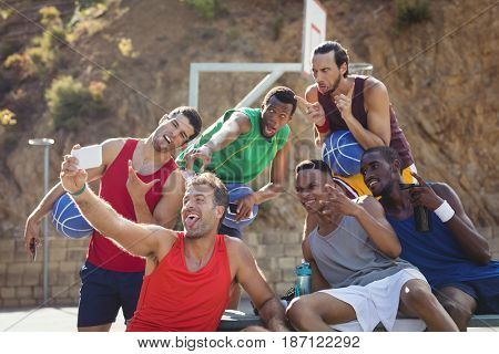 Basketball players taking a selfie in basketball court outdoors