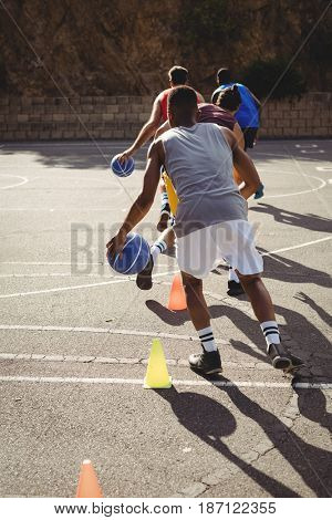 Basketball players practicing dribbling drill  in basketball court outdoors