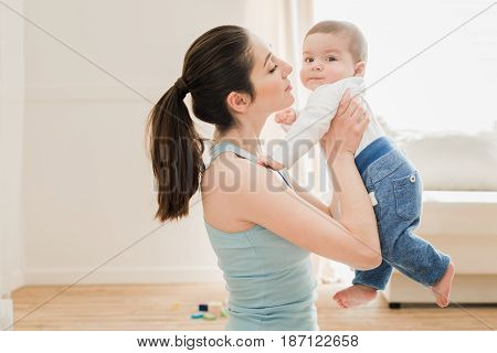 Young Mother Able To Kiss Her Son At Home In Sunny Day