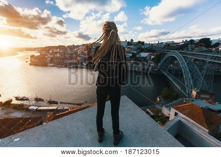 Girl with blonde dreadlocks standing on the background of the bridge Dom Luis I over Douro river, Porto, Portugal.