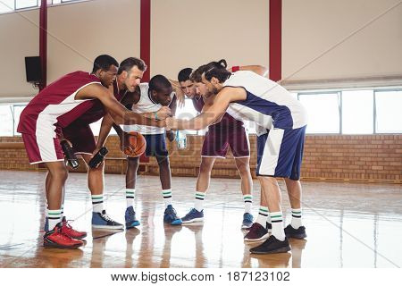 Determined basketball players forming a handstack in the court
