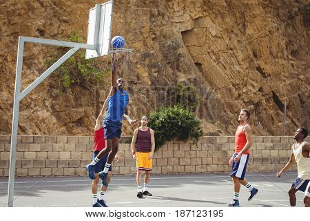 Basketball players playing basketball in the court outdoors