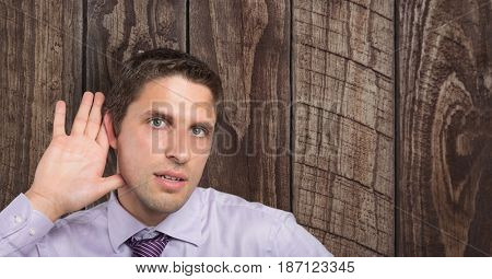 Digital composite of Businessman with hand on ear listening over wooden wall