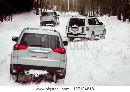Three SUVs in the woods in winter in the rally. Driving SUV car in winter on forest road with much snow