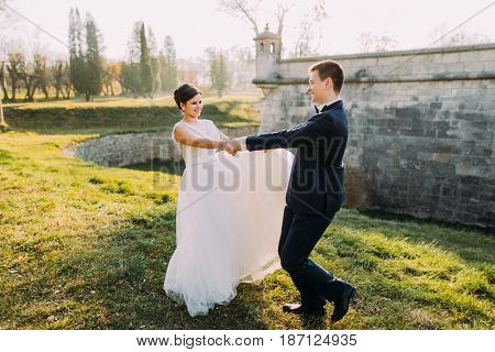 The emotional photo of the spinning round newlyweds at the background of the gothic castle