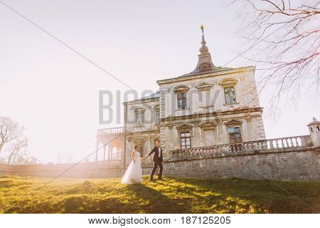 The horizontal full-length view of the stylish newlyweds holding hands while walking aroung the ancient gothic castle