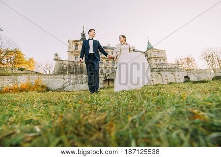 The time spending of the newlyweds couple in the garden of the mansion. The just married are holding hands. The down view