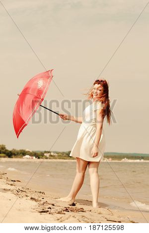Redhead woman wearing gauzy white dress walking on beach holding red umbrella having nice relaxing summertime walk