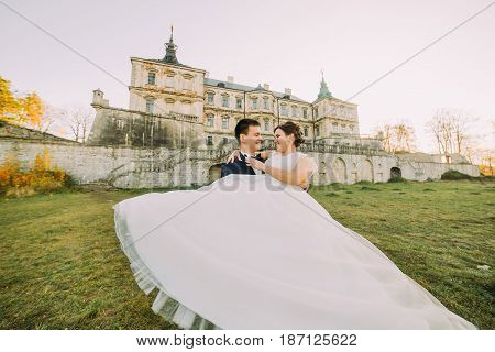 The close-up view of the groom spinning the happy bride round at the background of the old-fashioned castle