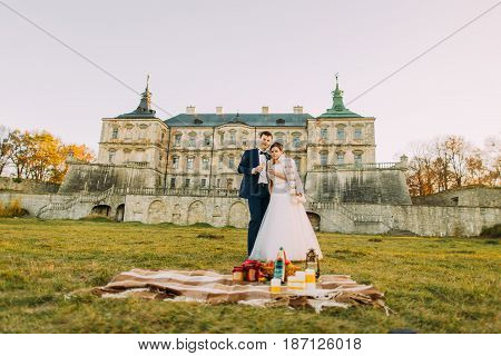 The horizontal view of the hugging newlyweds having the picnic in the meadow of the antique gothic castle during the sunset in the autumn.