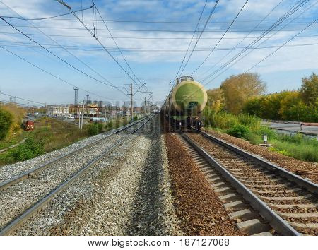 Two railways symmetrically receding to the horizon. Electrified railway tracks perspective with trees along. Departing cargo train away on right, approaching locomotive at left. Soft focus.