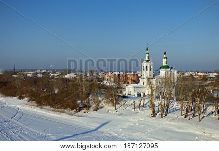 Church on the bank of frozen river. Lot of ski traces in the snow.  City at horizon. Winter landscape in Siberia, Russia.
