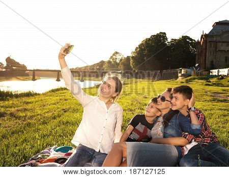 Summer scene of happy family taking selfies with smartphone in the park. Summer sunny day