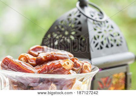 Closeup of Date fruits with Arabic lantern as background. Ramadan, Eid concept