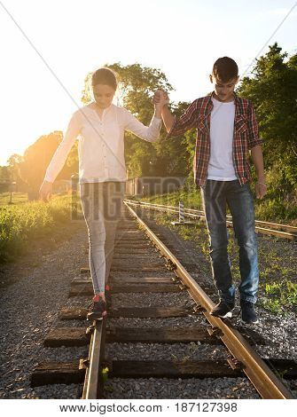 Happy Smiling Girl And Boy Walking With Holding Hands On Rails