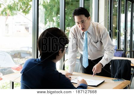 Asian manager of businessman complaining to employee by pointing to him for mistake work stressed feeling in cafe office