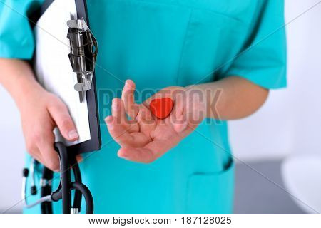 Female surgeon doctor with stethoscope holding heart.