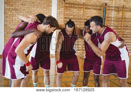 Basketball players forming a huddle in the court