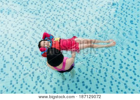 Top view of Asian Mother and child swimming in the pool. Happy mother teaching her daughter to swim. Little child learning and exercising in the water.