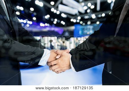 Auto business car sale deal gesture and people concept - Close up of male handshake in auto show or salon.