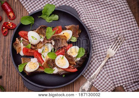 Baked eggplant with bacon, garlic and quail eggs on pan. Wooden background. Top view