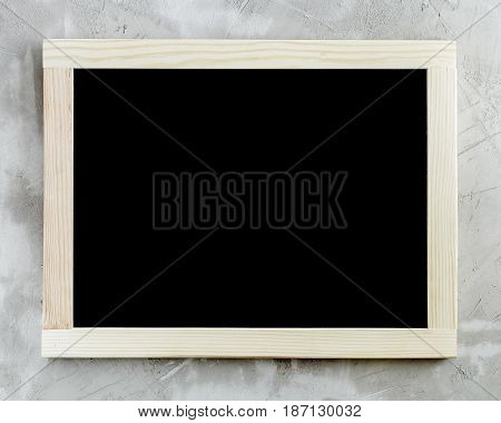 Blank black chalkboard with wooden frame on concrete background.