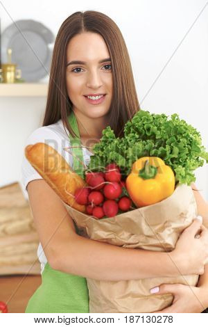 Young caucasian woman in a green apron is holding paper bag full of vegetables and fruits while smiling in kitchen.
