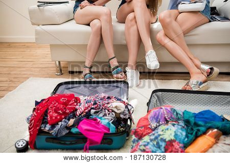Young Women Packing Suitcases For Vacation Together At Home, Suitcases Travel Concept