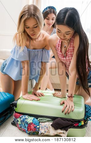 Young Women Packing Suitcase For Vacation Together At Home, Packing Luggage Concept