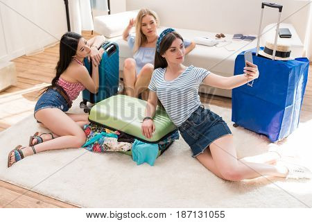 Young Women Packing Suitcases For Vacation And Taking Travel Selfie On Smartphone At Home, Packing L