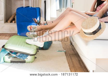 Young Women Packing Suitcases For Vacation Together At Home, Travel Bags Concept