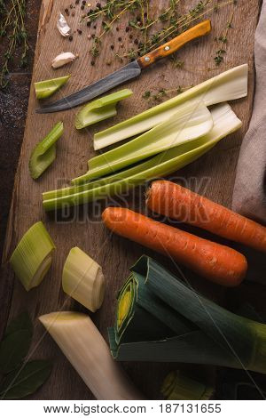 Carrots, celery, leeks on a wooden board horizontal