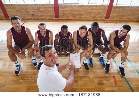 Portrait of smiling coach explaining game plan to basketball players in the court